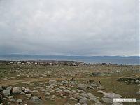 А если обернуться, картина будет такой: каменное поле, кромка берега с раскинувшимся на ней городочком, озеро, и вдалеке - горы противоположного берега.