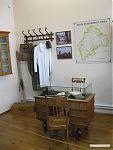 Кабинет уездного врача. Вешалка для одежды, и карта уезда на стене.