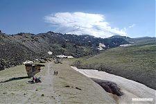 На переднем плане - плато с останцами, на заднем - укрытый шапкой облаков Эльбрус.