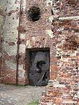 Входная дверь, покорёженная и насквозь пробитая снарядами.