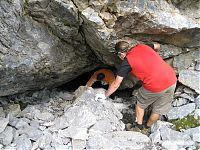 Спуск в пещеру выглядит примерно таким образом. Мы оттуда доставали заначку (верёвку, продукты, бензин и ещё пару нужных вещей, в том числе поюзанный, но вполне приличный комбез для парня в красной майке).