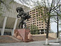 Кабба уулу Кожомкул, советский спортсмен-тяжеловес. На заднем плане - национальный Дворец спорта.