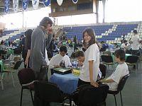 Столы расставлены на игровой площадке крытого стадиона, на котором играют в гандбол.